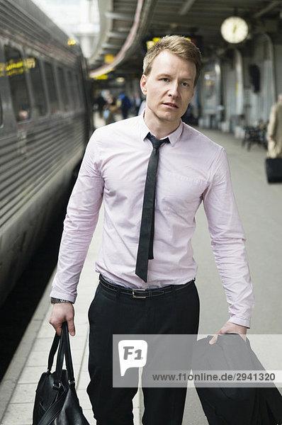 Mann mit dem Zug am Bahnhof