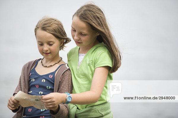 Zwei Mädchen Lesen Anweisungen aus einem Stück Papier