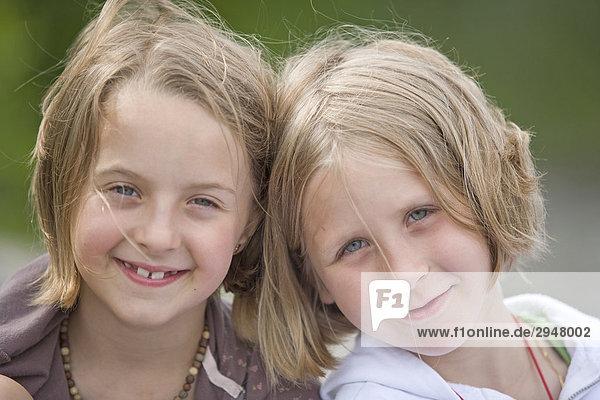 Portrait von zwei Mädchen sitzen nebeneinander