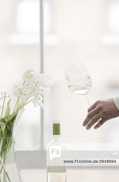 Glas Weißwein mit weißen Tulpen auf einem Felsvorsprung Fenster hält Hände