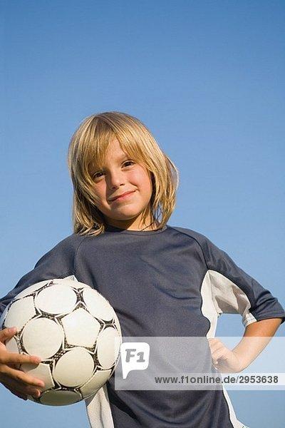 Boy posiert mit Fußball unter dem arm