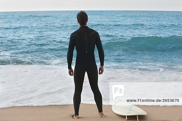 Surfer im Anzug stehen am Strand