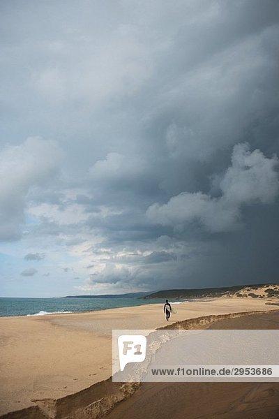 Mann zu Fuß auf dem Sand mit seinem Surfbrett auf stürmischer Tag