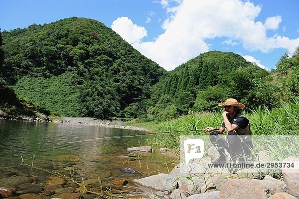 Man with straw hat sitting on stone and holding fishing rod