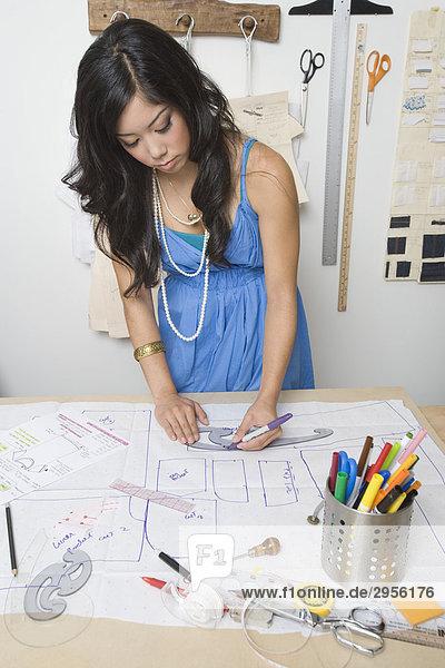 Modedesignerin die an Schreibtisch arbeitet