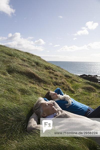 Älteres Paar das entspannt  Küstenlandschaft