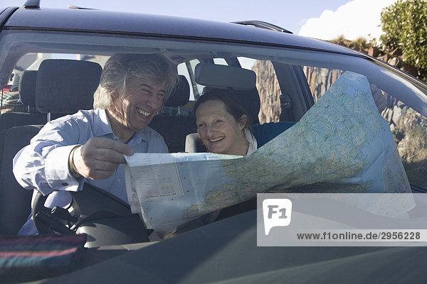 Älteres Paar das in Auto lachend über Karte sitzt