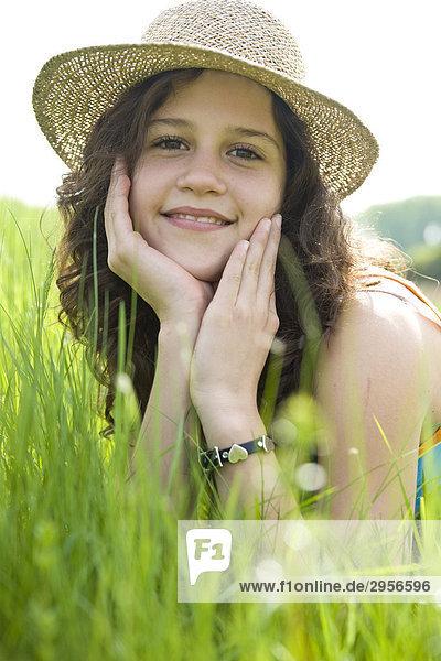 Junges Mädchen mit Strohhut auf sattgrüner Wiese liegend  Blick in die Kamera