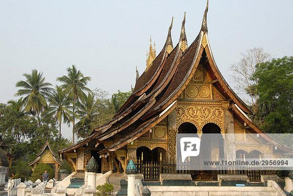 Nationalsymbol alter buddhistischer Tempel mit geschwungenem Dach vor Palmen  Kloster Wat Xieng Thong  Luang Prabang  Laos  Südostasien