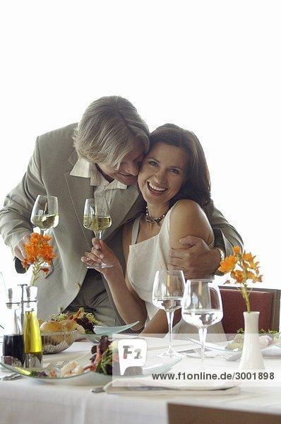 Paar am gedeckten Tisch mit Weingläsern