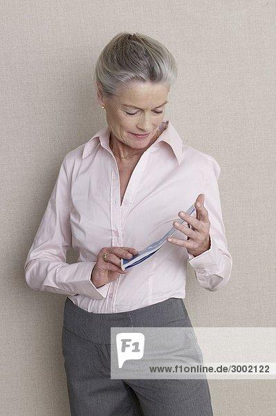 Seniorin im Businessdress mit Ticket