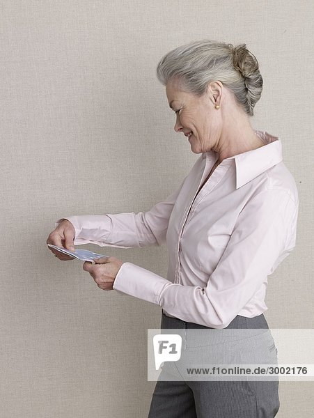 Senior adult in business clothing holding air ticket 64741