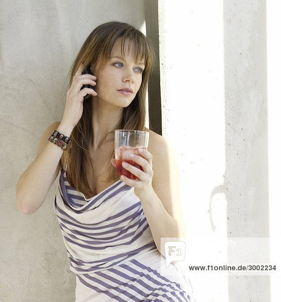 Woman is phoning with a cell phone and holding a glass