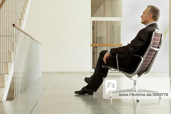 Geschäftsmann sitzt im Bürostuhl im Flur  München  Bayern  Deutschland
