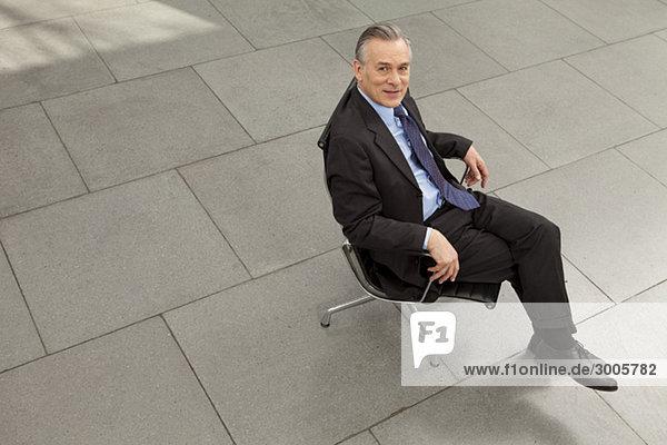 Geschäftsmann sitzt im Bürostuhl im Foyer  München  Bayern  Deutschland