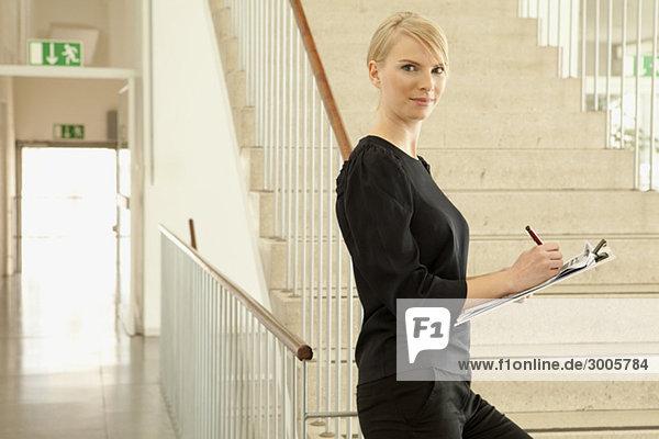 Frau mit Stift und Klemmbrett im Treppenhaus  München  Bayern  Deutschland