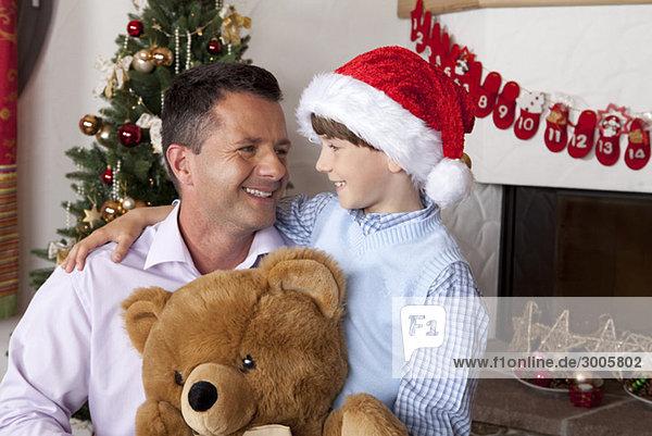Vater mit Sohn und Teddybär am Weihnachtsbaum
