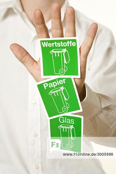 Mann zeigt drei Symbole zur Mülltrennung  Deutschland Mann zeigt drei Symbole zur Mülltrennung, Deutschland