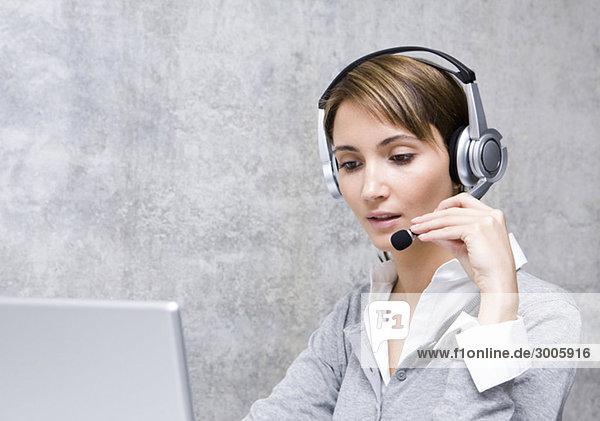 Frau in Büro mit Headset an Laptop