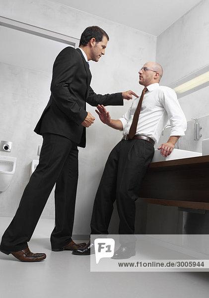 Zwei Geschäftsmänner streiten sich in der Toilette