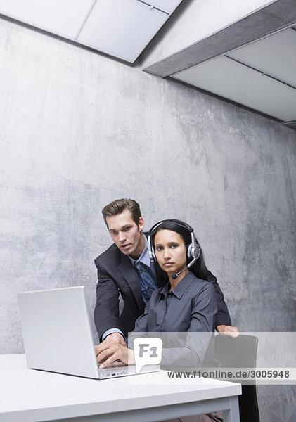 Frau und Mann in Büro mit Laptop und Headset