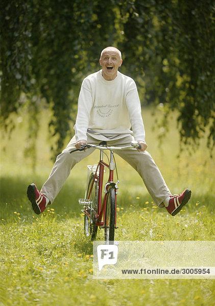 Lachender Senior fährt Fahrrad auf einer Wiese