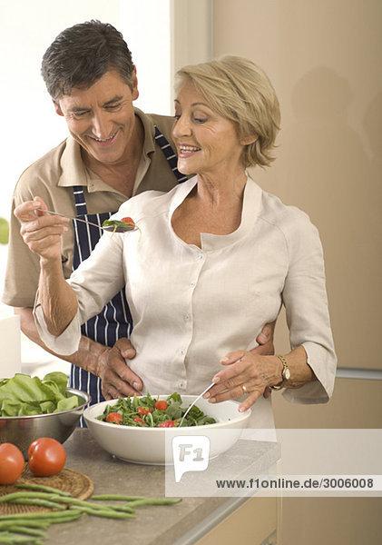 Älteres Paar in der Küche bereitet Salat zu