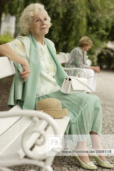 Seniorin sitzt auf Parkbank