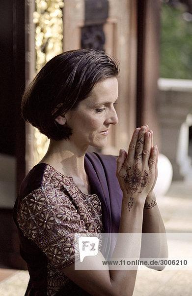 Dunkelhaarige Frau in einem Sari mit gefalteten Händen - Tradition - Gebet