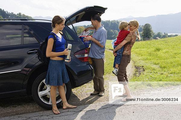 Familie am Auto  Gmund  Bayern  Deutschland