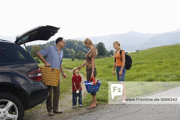 Familie mit Picknickkorb am Auto  Gmund  Bayern  Deutschland