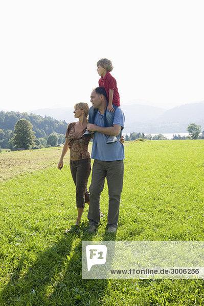 Familie spaziert über eine Wiese  Gmund  Bayern  Deutschland