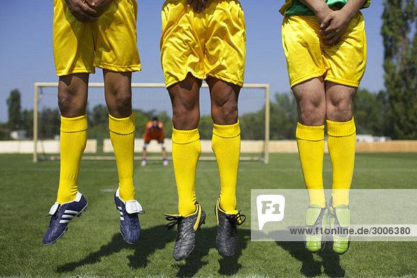Drei brasilianische Fußballspieler springen nach oben