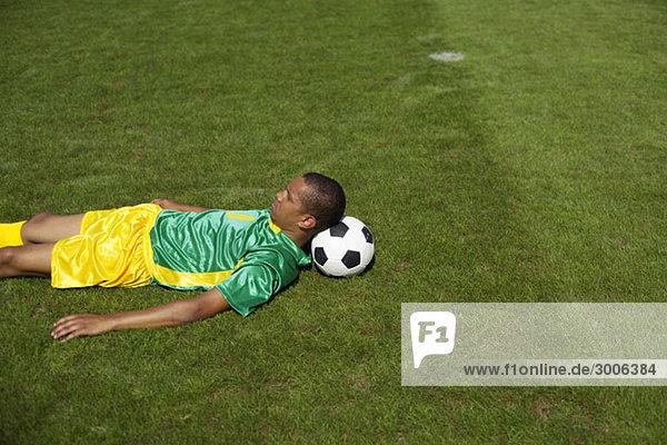 Erschöpfter brasilianischer Fußballspieler liegt auf Rasen