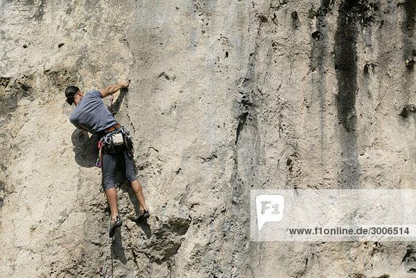 Mann klettert eine Felswand empor - Gefahr - Freizeitsport