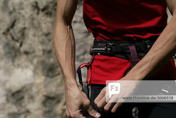 Klettergurt Englisch : Junger mann mit sehnigen armen berührt seinen klettergurt felswand