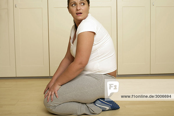 Overweight young woman in sportswear kneeling on the floor (part of)