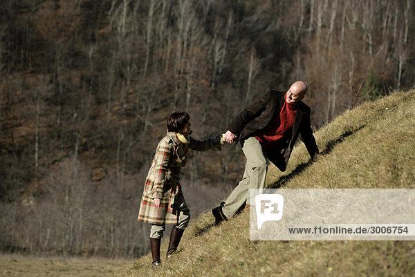 Älteres Paar steigt Hügel hinauf