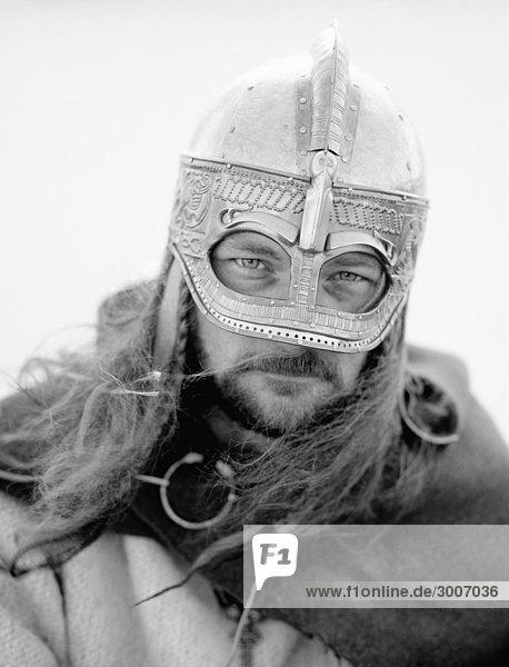 Eine Nahaufnahme von einem Viking mit langen Haaren und einen Helm