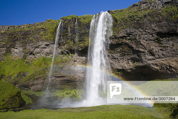 Island - gebildet Rainbow an einem Wasserfall (Seljalandsfoss Wasserfall)