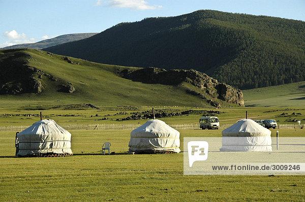 Drei Jurten Ger in der Steppe vor bewaldetem Grebirgszug Orkhon Wasserfall Mongolei