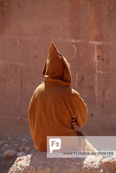 Mann sitzt auf Mauer in traditionellem Gewand Jelaba und spitzer Kapuze Tourbist Hoher Atlas Marokko