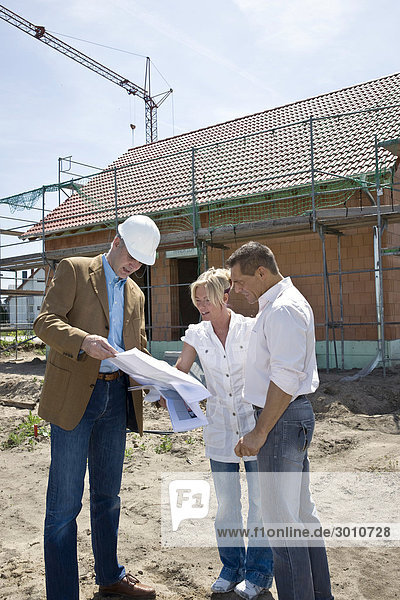 Paar unterhält sich mit einem Architekt auf einer Baustelle