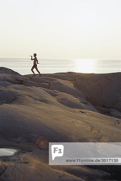 Silhouette einer Person auf einer Klippe in den Sonnenuntergang.