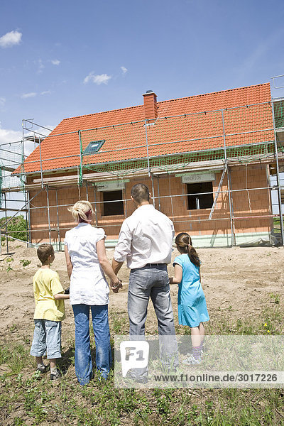 Familie mit zwei Kindern schaut auf die Baustelle eines Hauses  Rückansicht