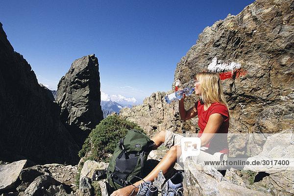 Eine Frau Trinkwasser sitzen auf einem Mountain Peak Korsika.