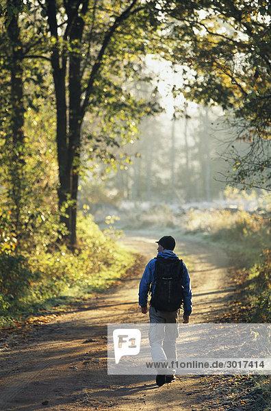 Ein Mann zu Fuß auf einer Landstraße Schweden.