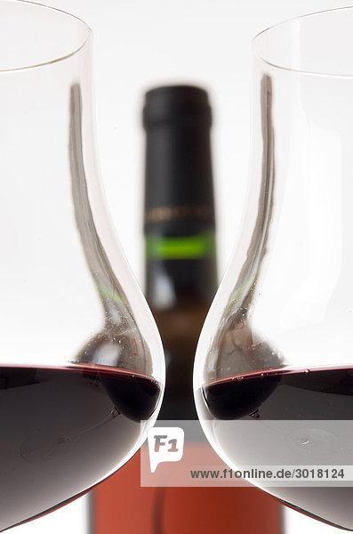 Zwei gefüllte Rotweingläser vor Weinflasche  Querschnitt Zwei gefüllte Rotweingläser vor Weinflasche, Querschnitt