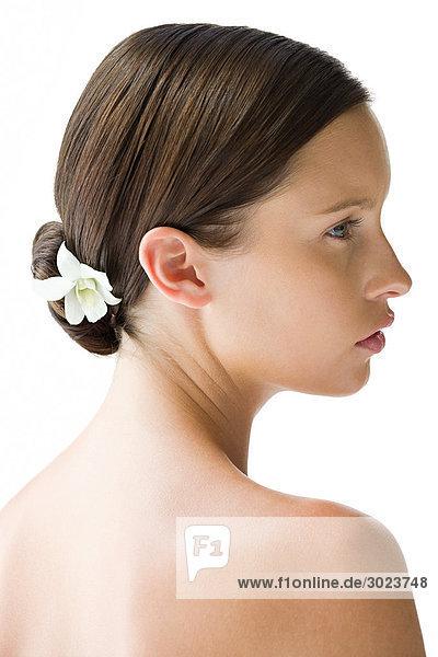 Porträt einer jungen Frau mit Blume im Haar
