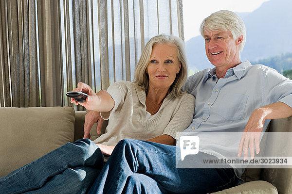 Mittelalterliches Paar  das zusammen auf der Couch sitzt und fernsieht.